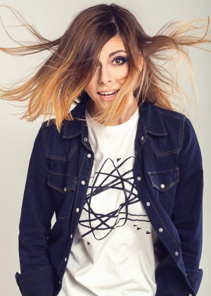 Cool smart teenager girl in jeans shirt with funny curious face